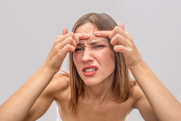 Irritated young woman stands and looks closer to mirror. she keeps fingers together and try to remove acne spot on forehead.
