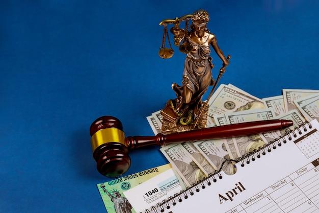 Форма irs. 1040 налоговых форм сша 15 апреля крайнего срока календарь налогового сезона, в то время как страницы сто долларовых купюр на столе весы правосудия, молоток