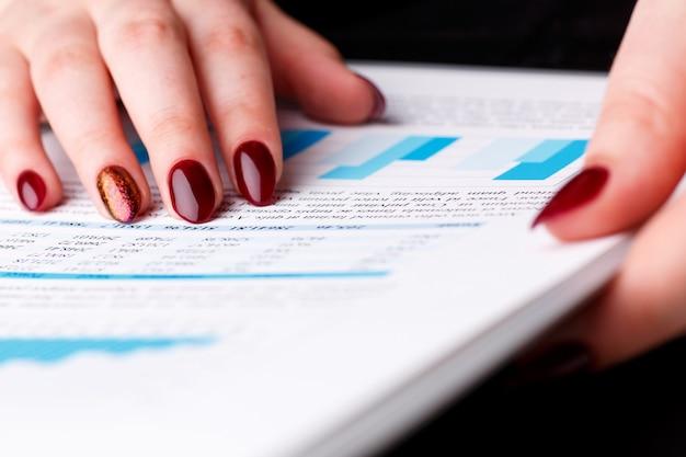 Женский палец точки руки в финансовой диаграмме разрешает и обсуждает крупный план проблемы. свежий взгляд на ситуацию совет совета советник по продажам советник изучить прибыль аудит работы работа фондового рынка irs инспектор