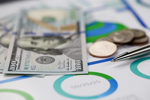 ホームオフィスの設定で机の現金ドルプロットに横たわっている銀のペン。家族の費用の計算社会所得人口フリーランスirs状況成長研究コンセプト