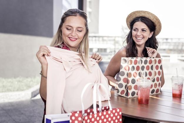 아름답습니다. 그녀의 친구와 함께 카페에 앉아있는 동안 그녀의 새 스웨터를보고 기쁘게 좋은 여자
