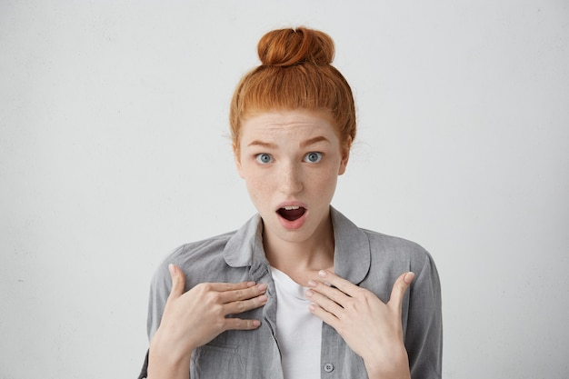 Is it me? shocked red-haired teenage girl with freckles and blue eyes pointing at herself with hands being surprised to be accused of something. lovely woman with shocked and astonished expression
