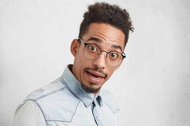 Is it really so? surprised mixed race male nerd looks in bewilderment wears round spectacles,