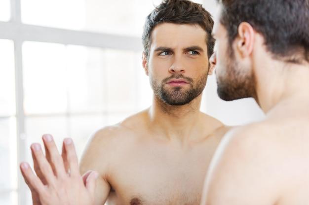 それはにきびですか?鏡に寄りかかって自分を注意深く見つめる真面目な若い上半身裸の男