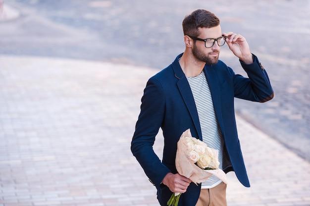 それは彼女ですか?花の花束を保持し、通りを歩いている間彼の眼鏡を調整するスマートカジュアルウェアのハンサムな若い男