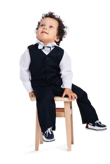 Is that a spider on the ceiling? little african baby boy looking up while sitting on stool against white background