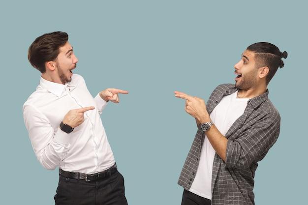 너야? 두 명의 잘생긴 웃긴 수염난 친구가 서서 놀란 얼굴로 서로를 가리키며 묻는 옆모습. 밝은 파란색 배경에 고립 된 실내 스튜디오 촬영.