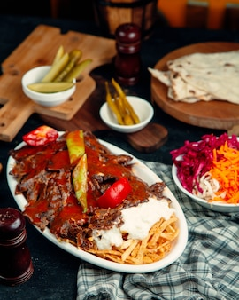 Iskender kebab garnished with tomato sauce, served with potato and yogurt