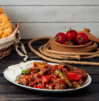 Iskender kebab garnished with tomato sauce, served with yoghurt