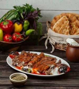 Iskender kebab garnished with tomato sauce and yoghurt, served with grilled vegetables