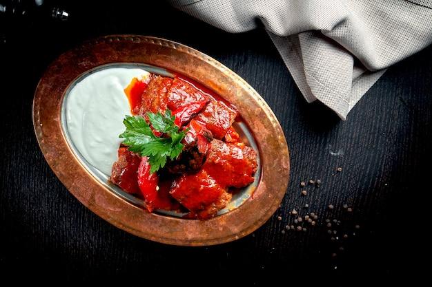 얇게 자른 양고기에 피타와 녹인 양의 우유 버터와 요구르트를 얹은 뜨거운 토마토 소스를 얹은 이스 켄더 케밥