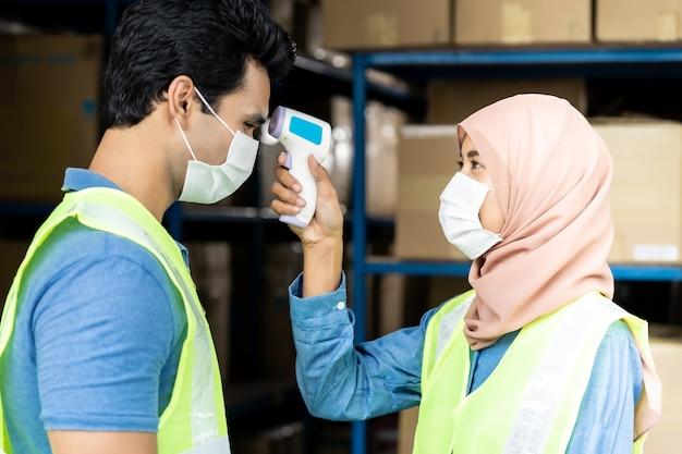 工場に入る前に労働者に温度を取っているイスラムのアジアの倉庫労働者