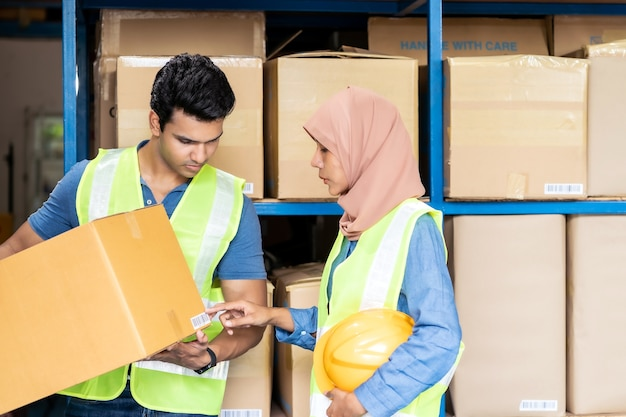 Islam asian warehouse worker working with indian warehouse worker about inventory