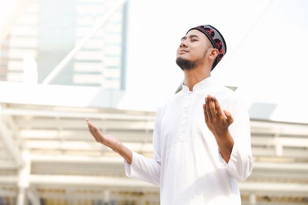 都市の背景で屋外で祈るイスラム教のイスラム教の若い男性