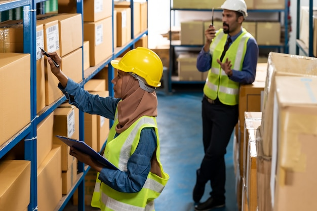 Islam warehouse worker do inventory with caucasian manager in background