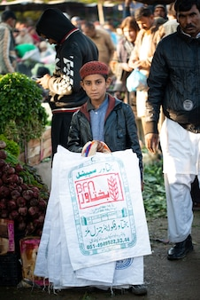 イスラマバード、イスラマバードキャピタルテリトリー、パキスタン-2020年2月2日、野菜市場で男の子がキャリーバッグを販売しています。