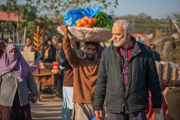 イスラマバード、イスラマバードキャピタルテリトリー、パキスタン-2020年2月2日、男性が野菜市場で顧客のために野菜を運んでいます。
