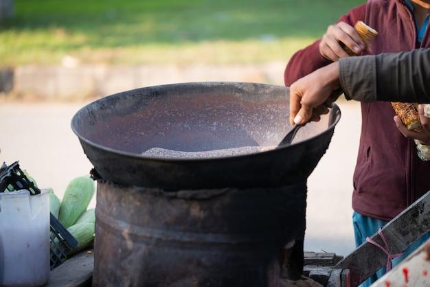 イスラマバード、イスラマバードキャピタルテリトリー、パキスタン-2020年2月2日、少年がお客様のために新鮮なトウモロコシを焙煎しています。