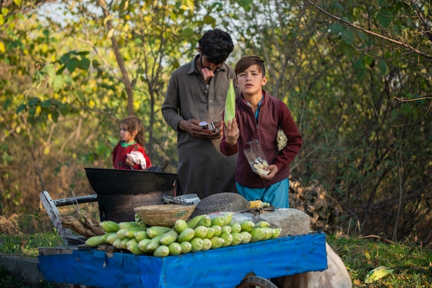 イスラマバード、イスラマバードキャピタルテリトリー、パキスタン-2020年2月2日、若い男の子がお客様のために新鮮なトウモロコシを焙煎しています。