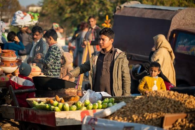 イスラマバード、イスラマバードキャピタルテリトリー、パキスタン-2020年2月5日、少年がお客様のために新鮮なトウモロコシを焙煎しています。