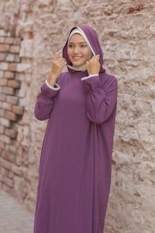 Исламская красивая женщина в мусульманском платье, стоя на фоне улицы парка летом деревья осенние деревья. всемирный день хиджаба.