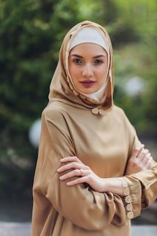 夏の公園の通りの背景の森の秋の木々に立っているイスラム教徒のドレスを着たイスラムの美しい女性
