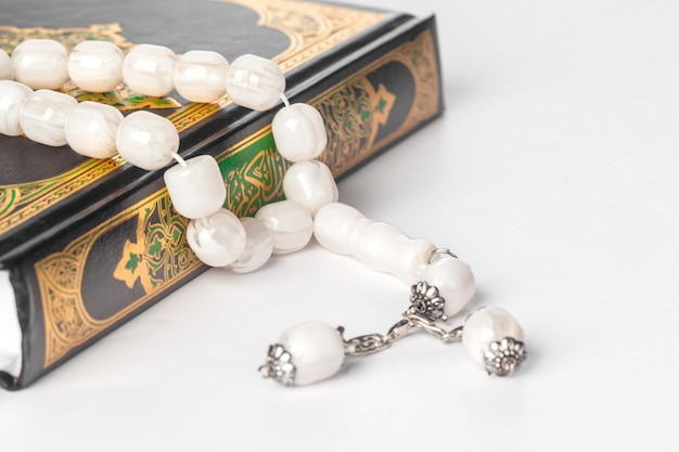 Islamic book holy quran and beads on withe