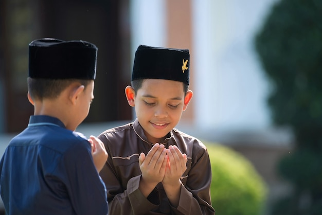 An islamic child prays to study with his sister and brother in a mosque in songkhla, thailand.