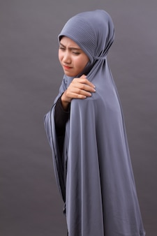Islamic muslim woman with shoulder or neck pain, stiffness, injury
