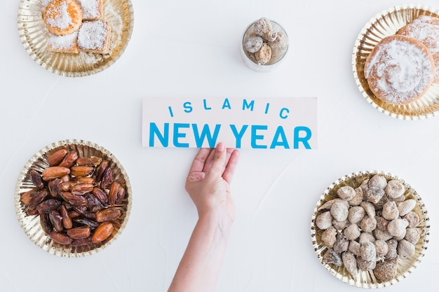 Islamic new year paper in hand and different desserts