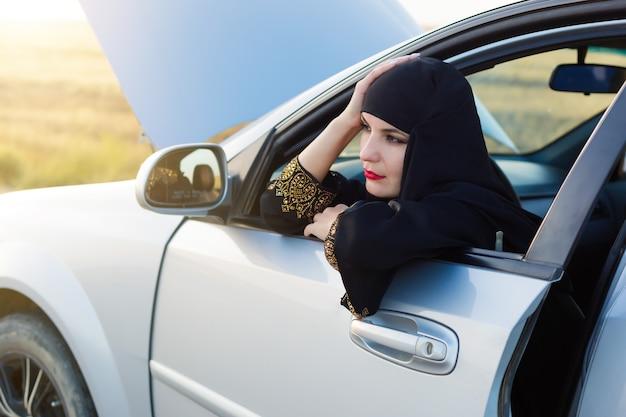 イスラムの女性と道路上の壊れた車