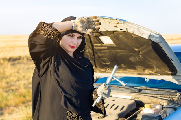 Исламская женщина-водитель ремонтирует машину на пустой дороге