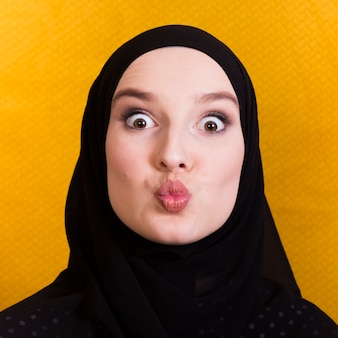 Islamic woman making funny face against yellow surface