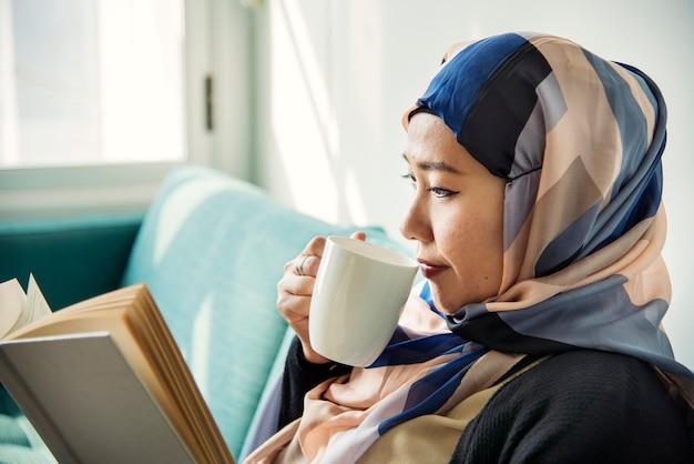 Islamic woman reading and drinking coffee