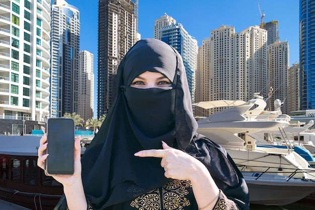 イスラムの女性は、街の背景に彼女の携帯電話で彼女の指を示しています。