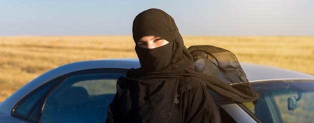 イスラムの女性が車の近くの太陽から目を細める