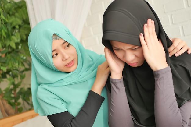 아픈 친구나 가족을 돌보는 이슬람 여성 그녀의 가장 친한 친구가 돌보는 아픈 두통 이슬람 이슬람 여성; 신뢰할 수 있는 친구 개념으로 고통받는 아픈 여자