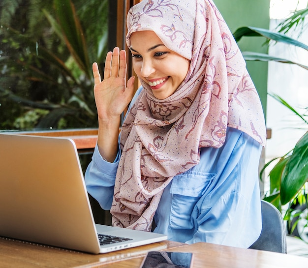 Islamic woman using laptop for video call with happy face