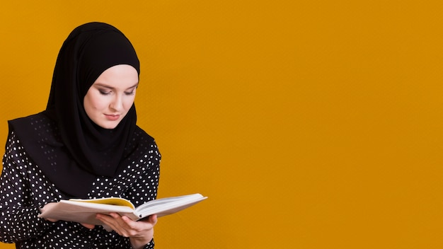 Islamic woman with headscarf reading book in front of background with copy space