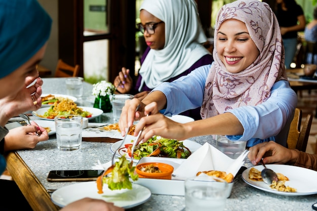 Islamic women friends dining together with happiness