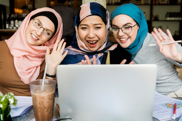 Islamic women friends using laptop for video call
