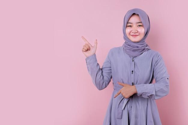 人差し指で指しているイスラムの若いアジアの女の子