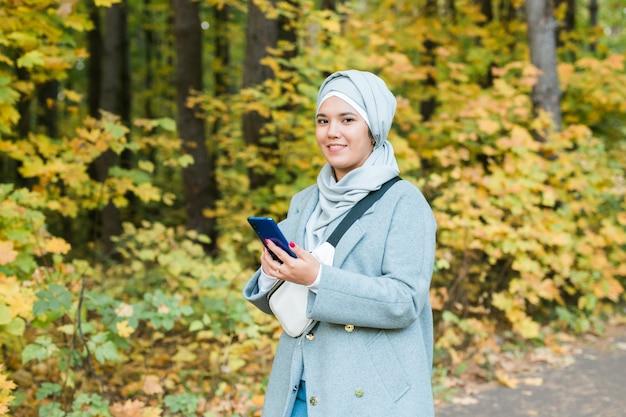 秋の公園の背景に立っているヒジャーブを身に着けているイスラムの若い女性。現代のアラビアのイスラム教徒の少女。