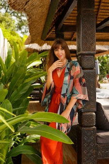 Island fashion.seductive stylish woman in bohemian summer clothes  posing in tropical luxury resort. vacation  concept.