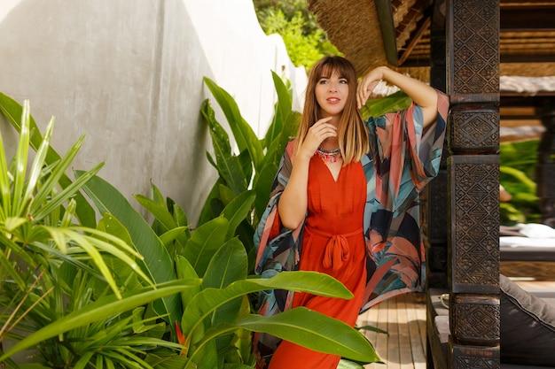 島のファッション。熱帯の高級リゾートでポーズをとって自由奔放な夏服で魅惑的なスタイリッシュな女性。休暇の概念。