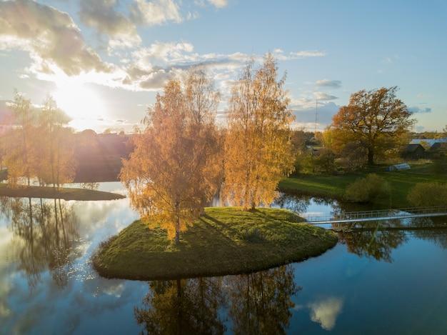 晴れた秋の日に湖にオレンジ色の白樺の木がある島
