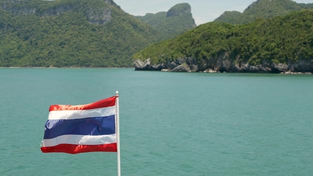 Острова в океане в национальном морском парке анг тонг. развевающийся флаг таиланда как национальный символ.