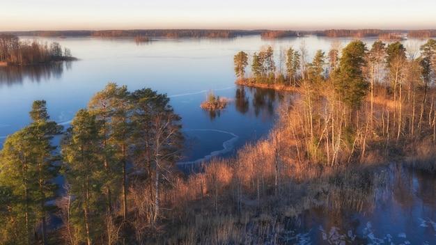 Острова на замерзшем озере вуокса в ленинградской области недалеко от города приозерск поздней осенью, вид с воздуха с дрона