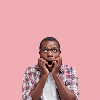 Изоляционный снимок удивленного красивого темнокожего мужчины в очках, держащего руки под подбородком, широко раскрытого рта, с удивлением смотрит вверх на пустое место для копии