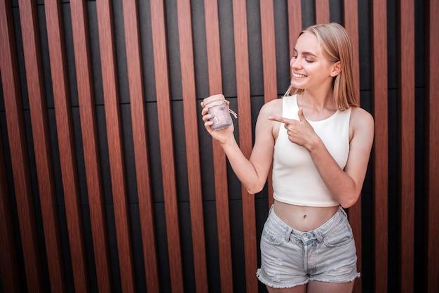 Позитивные блондинка девушка смотрит на банку десерта она держит в руке. она указывает на это. молодая женщина выглядит счастливой. isoated на полосатый фон.